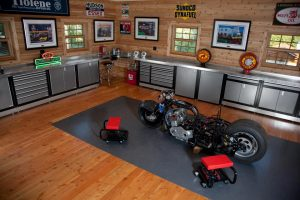garage with steel cabinets and wood walls and motorcycle