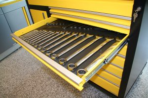 yellow cabinet with wrenches in the tray